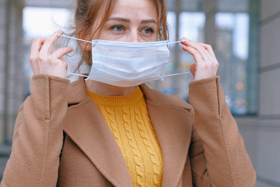 Kvinne som tar på munnbind
